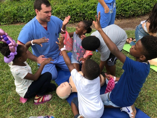 Medical Student teaching CPR to children at Community Fest - NSU