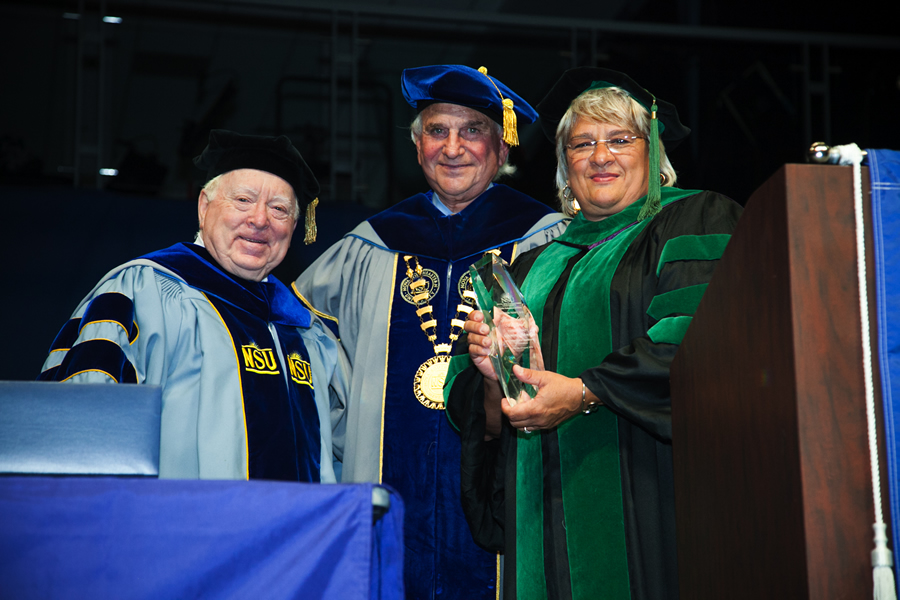 Elaine Wallace accepting her award from Frederick Lippman, R.Ph., Ed.D., Health Professions Division chancellor (far left), and George L. Hanbury II.